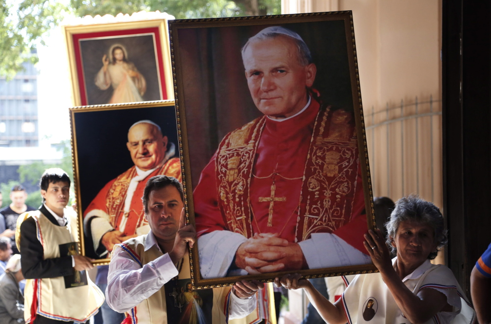 "Catholics at ""La Encarnacion"" church in Asuncion, Paraguay, hold posters of Popes John Paul II, right, and John XXIII to celebrate the historic day, with Popes Francis and Benedict XVI honoring John XXIII and John Paul II."