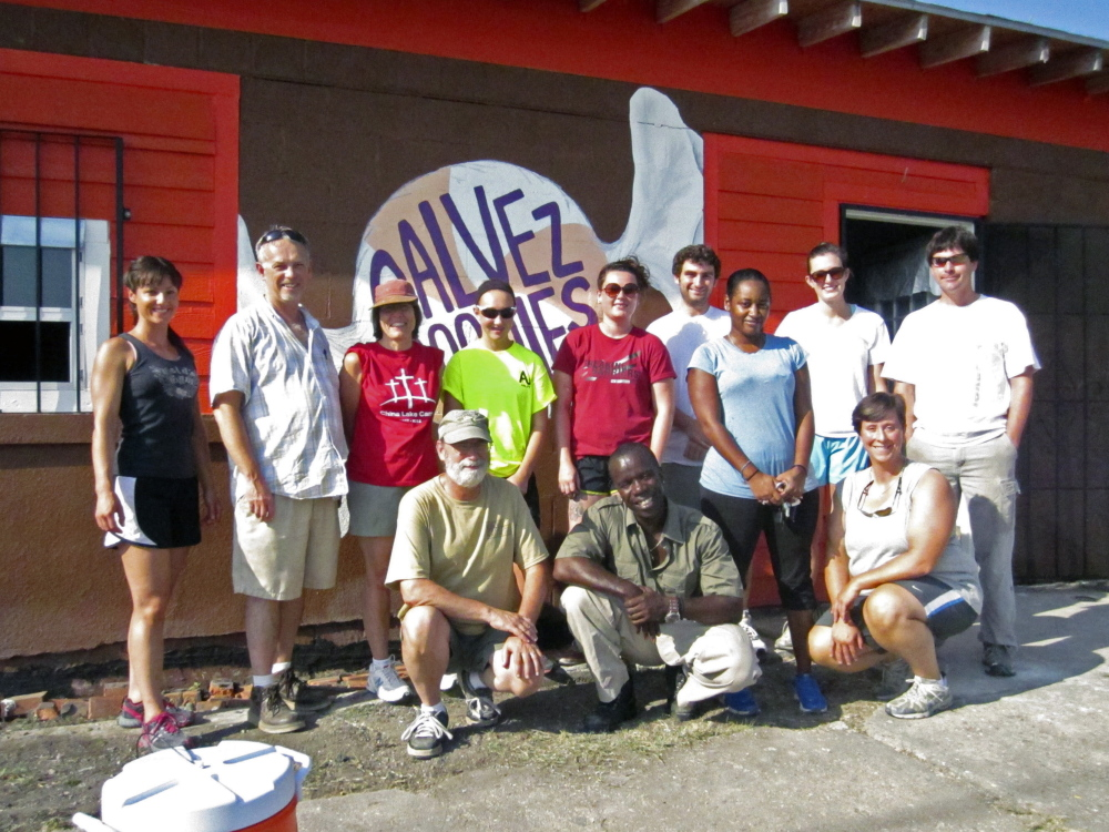 Last year: The Rev. Gary York, pastor of Oakland United Baptist Church, standing second from left; Ted Chaffee, pastor of Gardiner First Baptist Church, kneeling at left; Burnell Cotlon, kneeling at center; Kesha Cotlon, standing third from left; and Emily Webber, kneeling at right, pose with the 2013 mission trip group to New Orleans' Lower 9th Ward in front of the Cotlons' store, Galvez Goodies, which they helped repair.