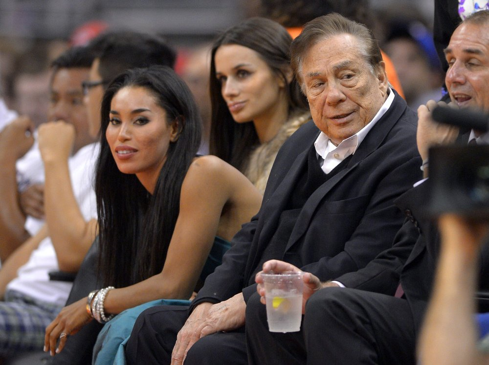 In this photo taken on Friday, Oct. 25, 2013, Los Angeles Clippers owner Donald Sterling, right, and V. Stiviano, left, watch the Clippers play the Sacramento Kings during the first half of an NBA basketball game in Los Angeles.