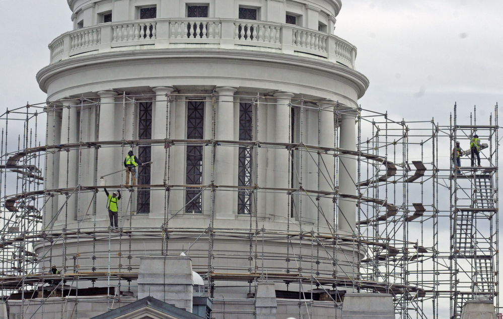 Prep: Workers build scaffolding around the State House dome on Wednesday in Augusta. This is the first part of a project to replace the old copper dome on the Capitol.