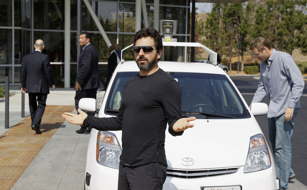 FILE - In this Sept. 25, 2012, file photo, Google co-founder Sergey Brin gestures after riding in a driverless car with officials, to a bill signing for driverless cars at Google headquarters in Mountain View, Calif. Google engineers say they have turned a corner in their pursuit of creating a car that can drive itself. Test cars have been able to navigate freeways comfortably for a few years. On Monday, April 28, 2014, Google said the cars can now negotiate thousands of urban situations that would have stumped them a year or two ago.