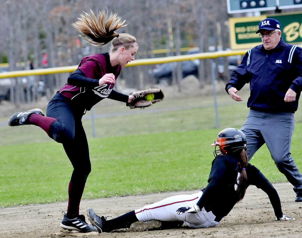 Staff photo by David Leaming Winslow's Brooke Haskell slides safe into second base as Nokomis' Becky Orcutt fields the throw in Winslow on Monday, April 28, 2014.