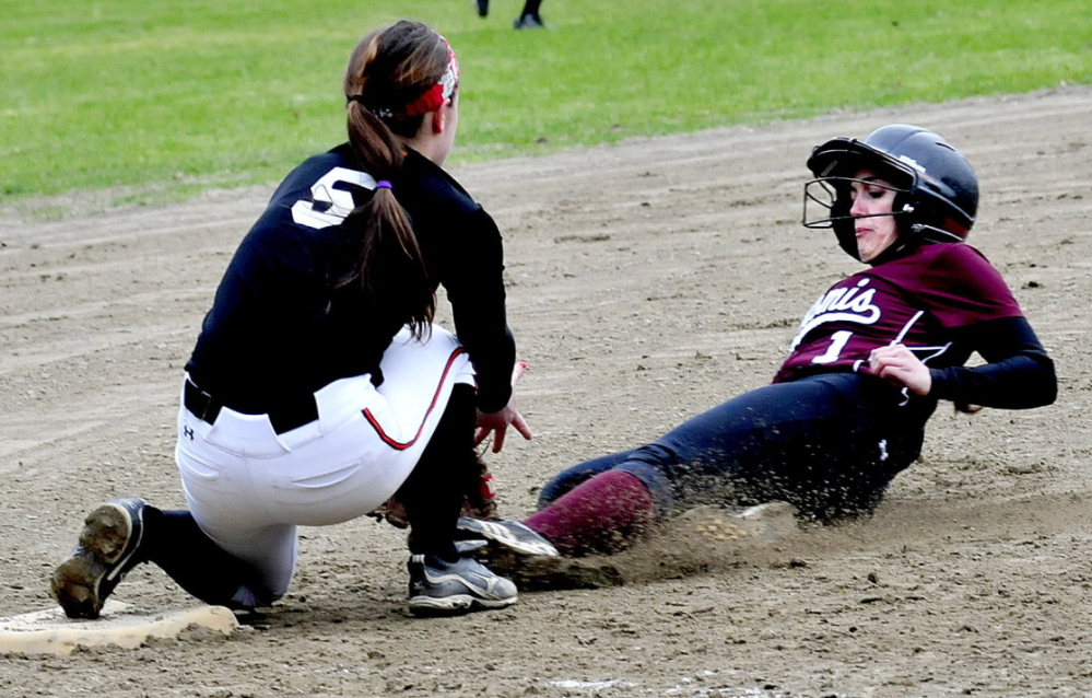 Staff photo by David Leaming Nokomis' Mikayla Charters slides into third base in time as Winslow's Brooke Haskell attempts to tag her out in Winslow on Monday, April 28, 2014.