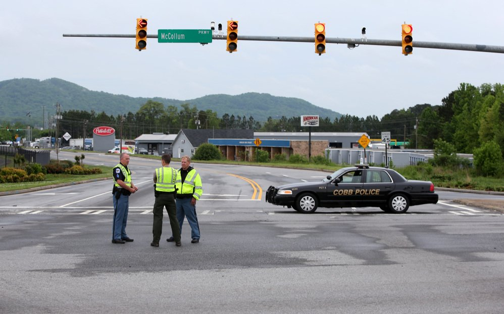 Cobb County police block off Old U.S. Highway 41 after a shooting at the Airport Road FedEx facility Tuesday morning in Kennesaw, Ga.
