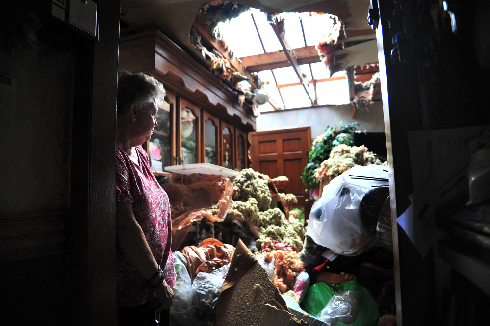 Faye Busby looks over her living room after a tornado ripped part of the roof off of her home in Graysville, Ala., Tuesday.