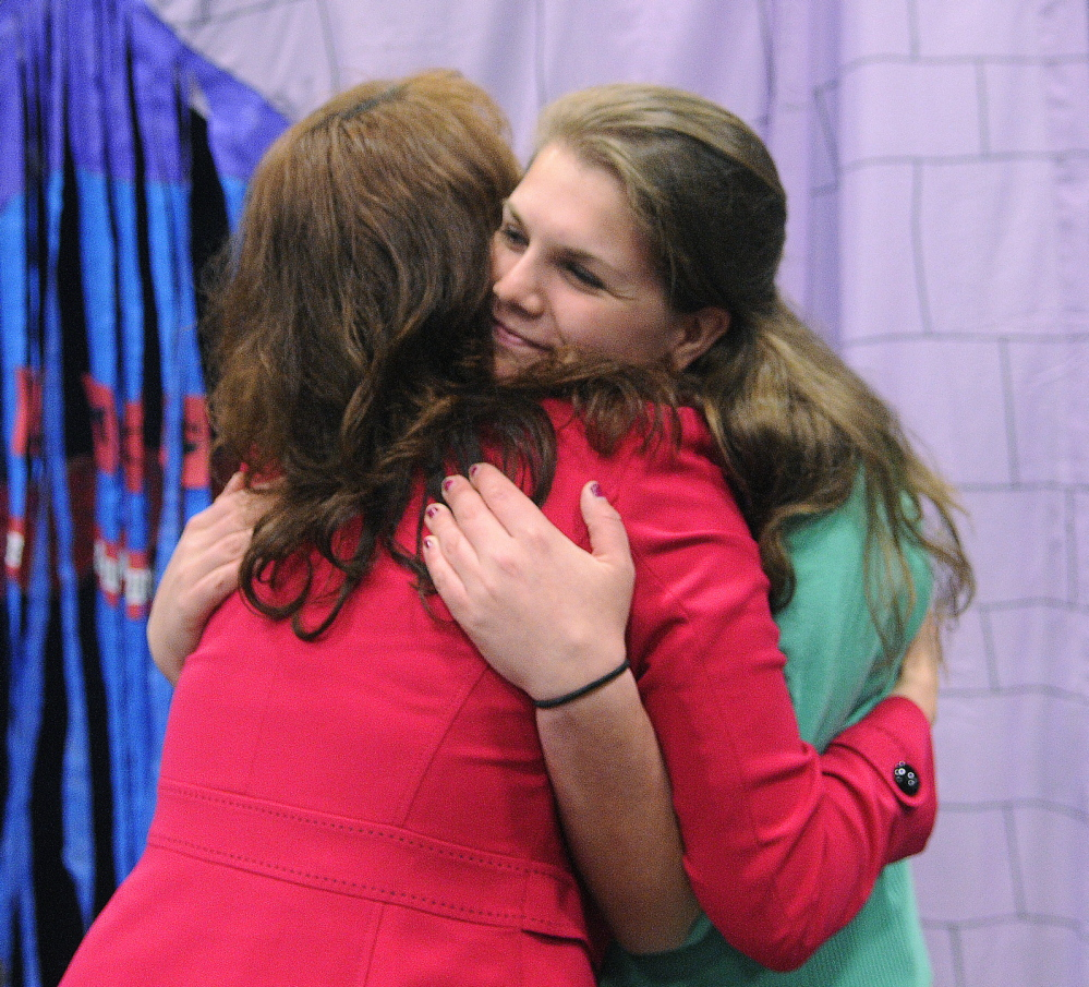 GETTING A BOOST: Messalonskee High School student Kaitlin Eschenbrenner, right, gets a hug Wednesday from teacher Tracie Travers during the annual Jobs for Maine's Graduates Career Development Conference. Eschenbrenner won a scholarship during the daylong conference in Augusta.