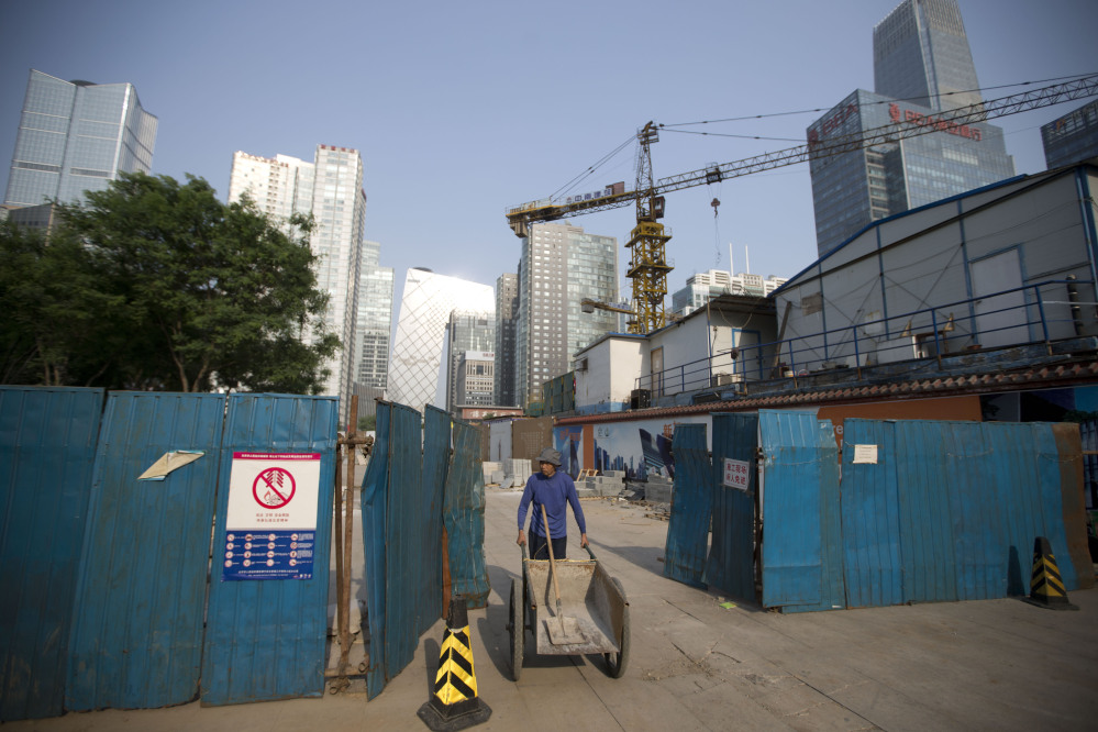 A worker pushes a cart as he walks out from a construction site at the Central Business District in Beijing Tuesday. The International Monetary Fund raised its economic growth forecast for China on Monday but warned that its financial system faces risks due to the rapid expansion of debt.