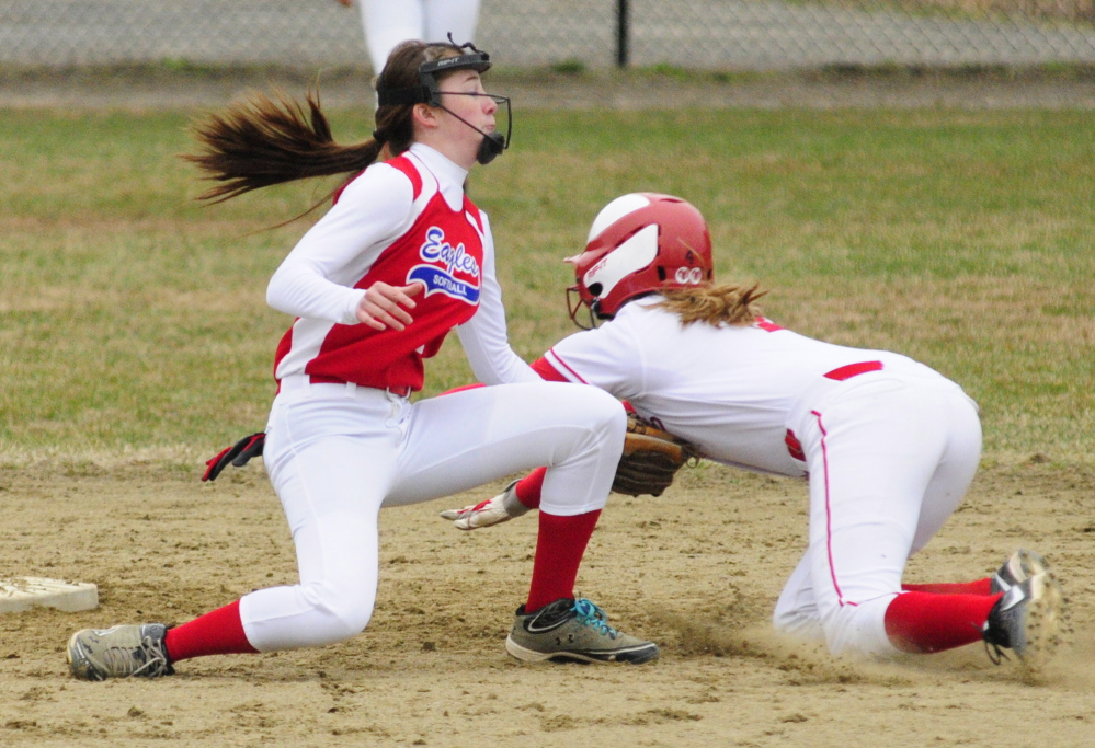 Staff photo by Joe Phelan Messalonskee shortstop Maddi Charest tags out Cony baserunner Michaela Dostie in front of second base during a game on Wednesday April 30, 2014 at Cony Family Field in Augusta.