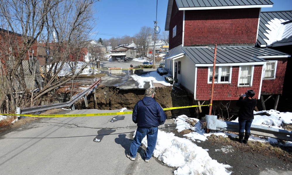 TEETERING: People stand on April 16 by the edge of the washed-out connector street between Main Street and Water Street in downtown Dexter, across the chasm from the Dexter Historical Society Grist Mill Museum, which teetered on the edge of the washout.
