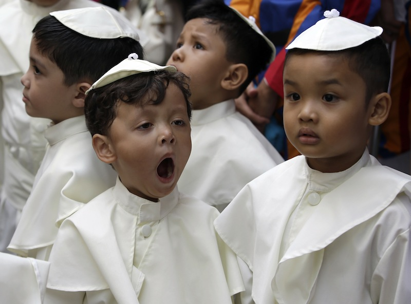 A boy dressed as a pope yawns as he prepares to join a parade in celebration of the canonization or the elevation to sainthood of Roman Catholic Pope John Paul II and Pope John XXIII Sunday at suburban Quezon city, northeast of Manila, Philippines.