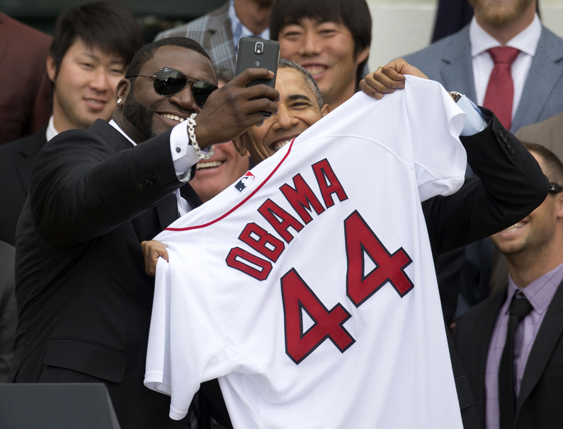 """Boston Red Sox player David """"Big Papi"""" Ortiz takes a selfie with President Barack Obama while holding a Boston Red Sox jersey presented to the president at the White House on Tuesday. Obama's jersey number reflects that he's the 44th president."""