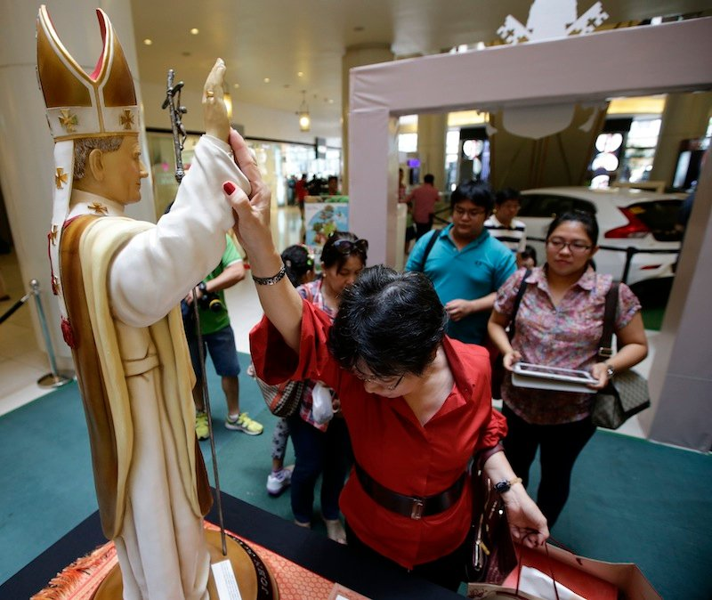A devotee touches to pray at the statue of Roman Catholic Pope John Paul II on display with other relics of the late pope as well as Pope John XXIII in celebration of their canonization or the elevation to sainthood Sunday at suburban Quezon city, northeast of Manila, Philippines.