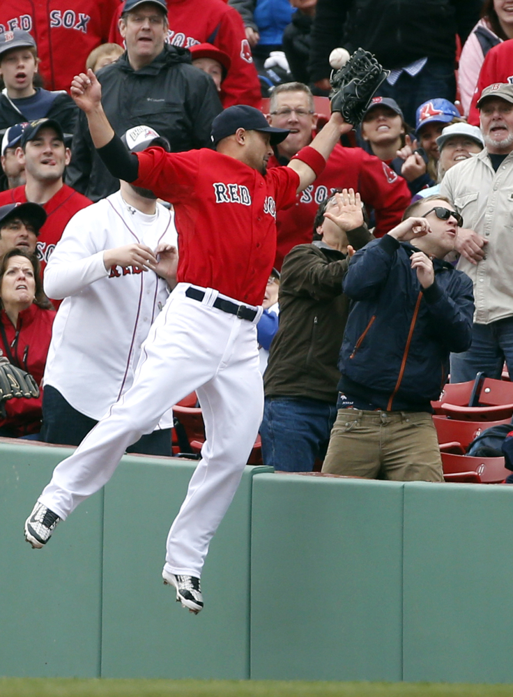 Boston Red Sox right fielder Shane Victorino jumps but cannot catch a fly that fell foul in the fourth inning in the first game of a doubleheader at Fenway Park on Thursday. The fly was hit by Rays right fielder Wil Myers.