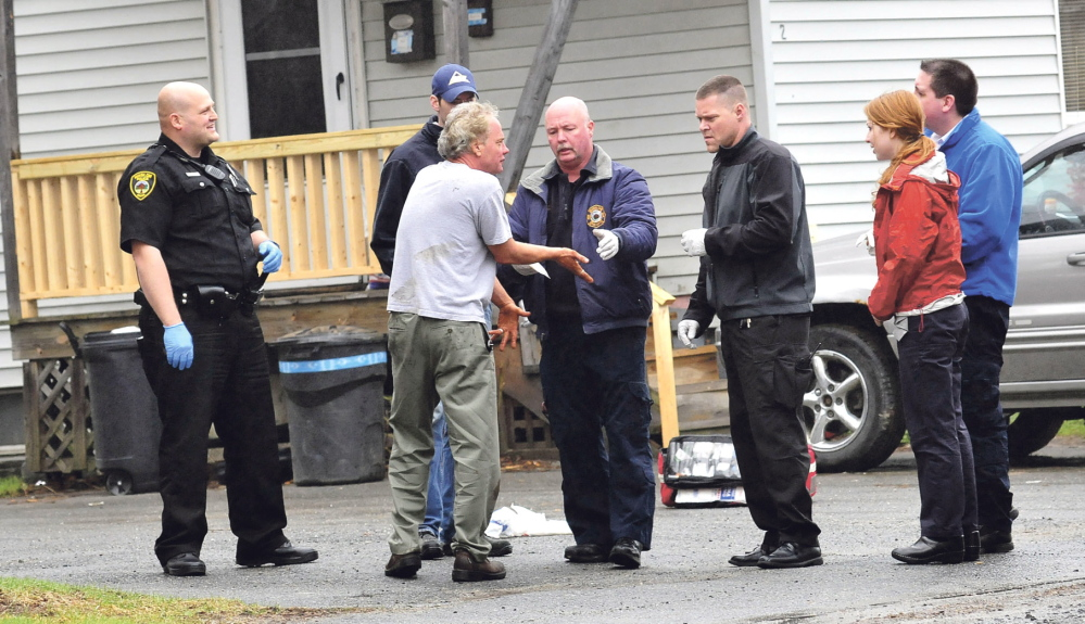 BLOODY SCENE: Winslow rescue and Delta Ambulance personnel treat a man whose hands and face were bloodied after he broke windows and damaged doors with a snow shovel at an apartment building at 92 Clinton Ave. in Winslow on Thursday. Winslow police officers Scott Christiansen, left, and Brandon Lund stand by.