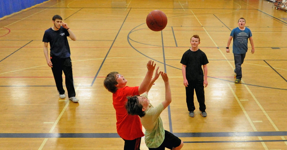Pick-up: Cameron Goodwin, 12, left center, battles for the rebound with Nelson Reynolds, 12, center, during a game of pick-up basketball at the Alfond Youth Center in Waterville on Thursday. The Alfond Youth Center in Waterville will celebrate its 90th anniversary May 30 at the center's annual dinner.