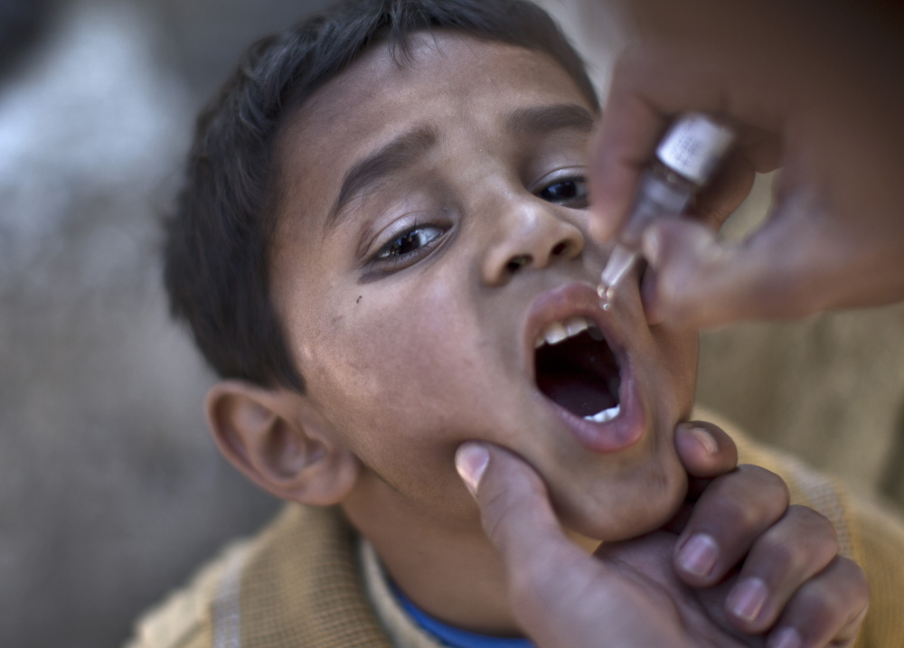 A Pakistani child is vaccinated against polio by a health worker in Islamabad, Pakistan, in this November 2013 photo. The ongoing effort to erradicate polio costs about $1 billion a year.