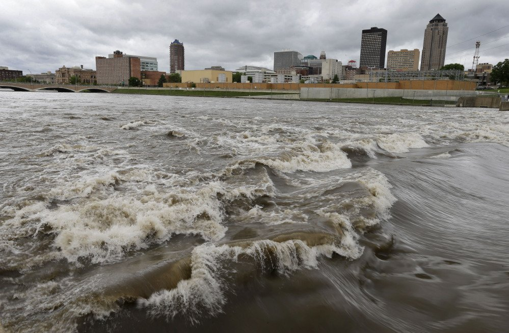 In this May 30, 2013, file photo, water splashes over the Center Street Dam in the swollen Des Moines River in downtown Des Moines, Iowa.