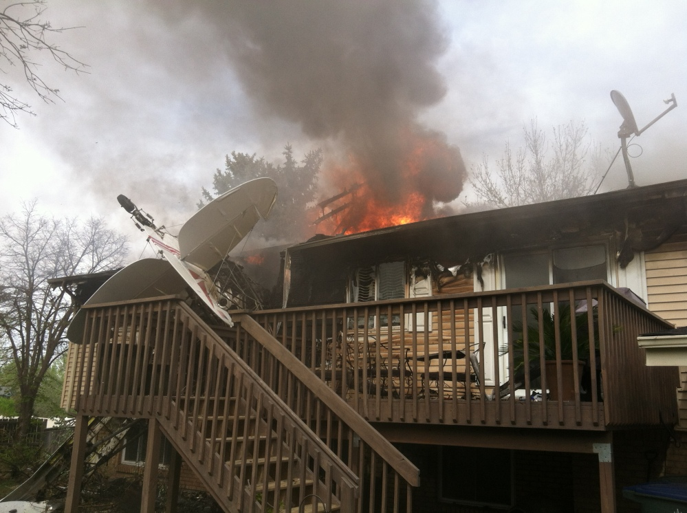 This photo provided by North Metro Fire Rescue District shows a house on fire after a plane crashed into it in Northglenn, Colo., Monday. The pilot, Brian Veatch, once owned the home, as indicated by property records. Veatch tried to put out the fire with a garden hose before he was forced away by burning fuel.