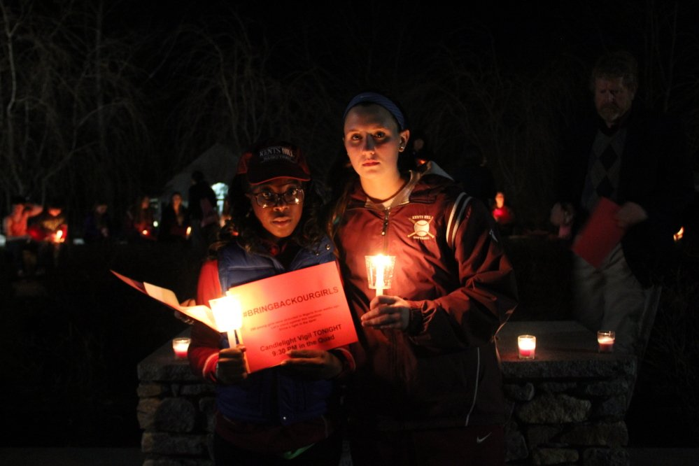 CALLING ATTENTION: Kents Hill School juniors Karrisha Gillespie, left, and Emma Curnin organized a vigil at the school on Tuesday night for Nigerian girls who have been kidnapped by an Islamic militant group.