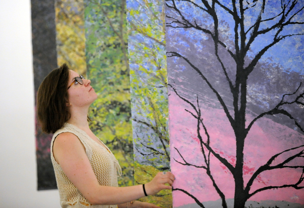 NEW EXHIBIT: Rachel McDonald, program manager at Common Street Art Gallery, arranges paintings by Readfield artist Christine Higgins at Common Street Art Gallery in downtown Waterville on Wednesday.