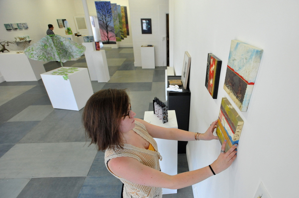LOCAL ART: Rachel McDonald, program manager at Common Street Art Gallery, hangs pieces by Readfield artist Christine Higgins, at Common Street Art Gallery in downtown Waterville on Wednesday.