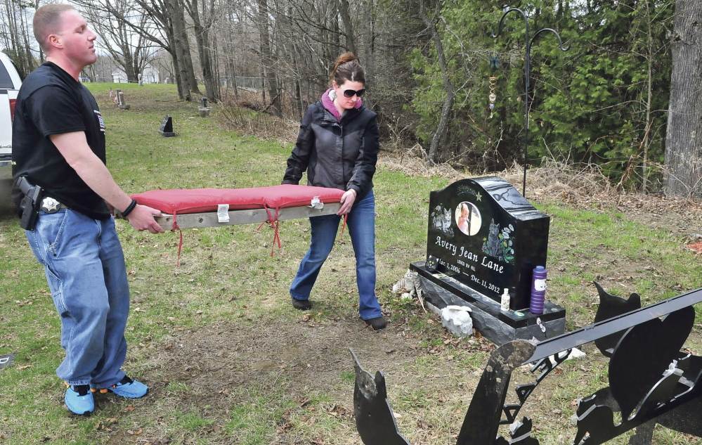 TIDYING UP: Kennebec County sheriff's Deputy Jacob Pierce and Tabitha Souzer on Tuesday return a cushion to the bench that was thrown down an embankment near the grave site of Souzer's daughter, Avery Lane, in the Friends Cemetery in Fairfield.