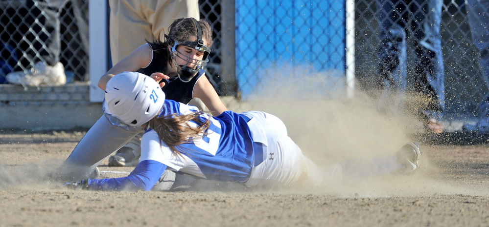 Staff photo by Michael G. Seamans Dirigo High School's Emma Lueders, 2, tags out Madison High School's Erin Whalen, 27, at third base in Madison on Wednesday. Madison defeated Dirigo 12-0 in six innings.