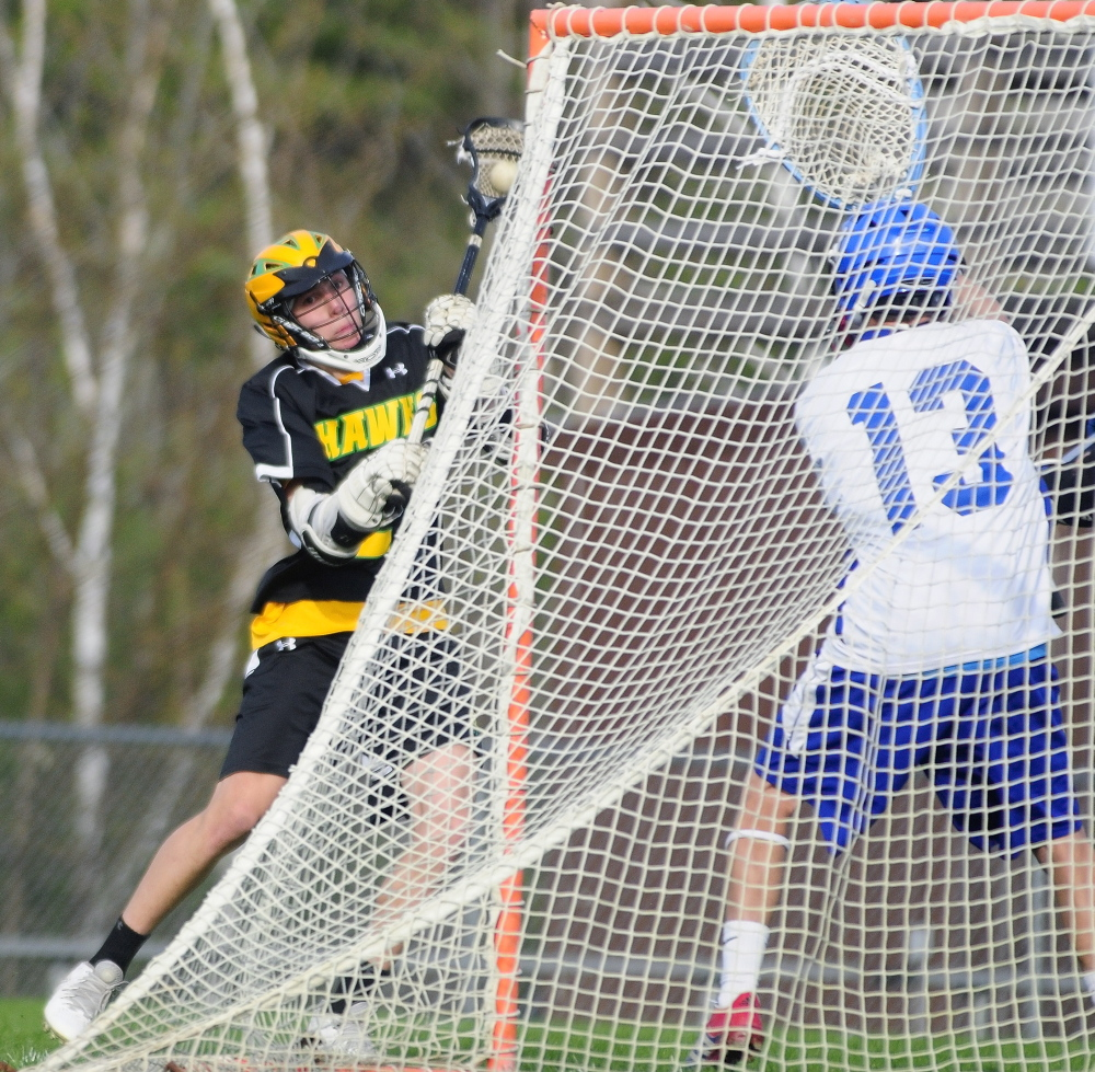 IT'S GOOD: Maranacook/Winthrop's Toby Smith shoots on Oak Hill keeper Matty Martin to score the Hawk's 12th goal Thursday in Wales.