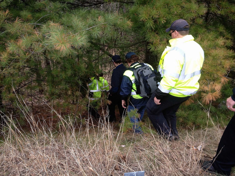 Searchers looking for Jaden Dremsa walk down a steep bank into the woods along Route 5 in North Waterboro on Friday.