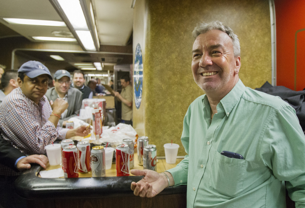 "Mark DeMonte, right, of Wallingford, Conn., joins other riders in the bar car on the train to New Haven, Conn. DeMonte, a bar car regular, has been dubbed ""Mayor of the 5:48"" by friends and riders."