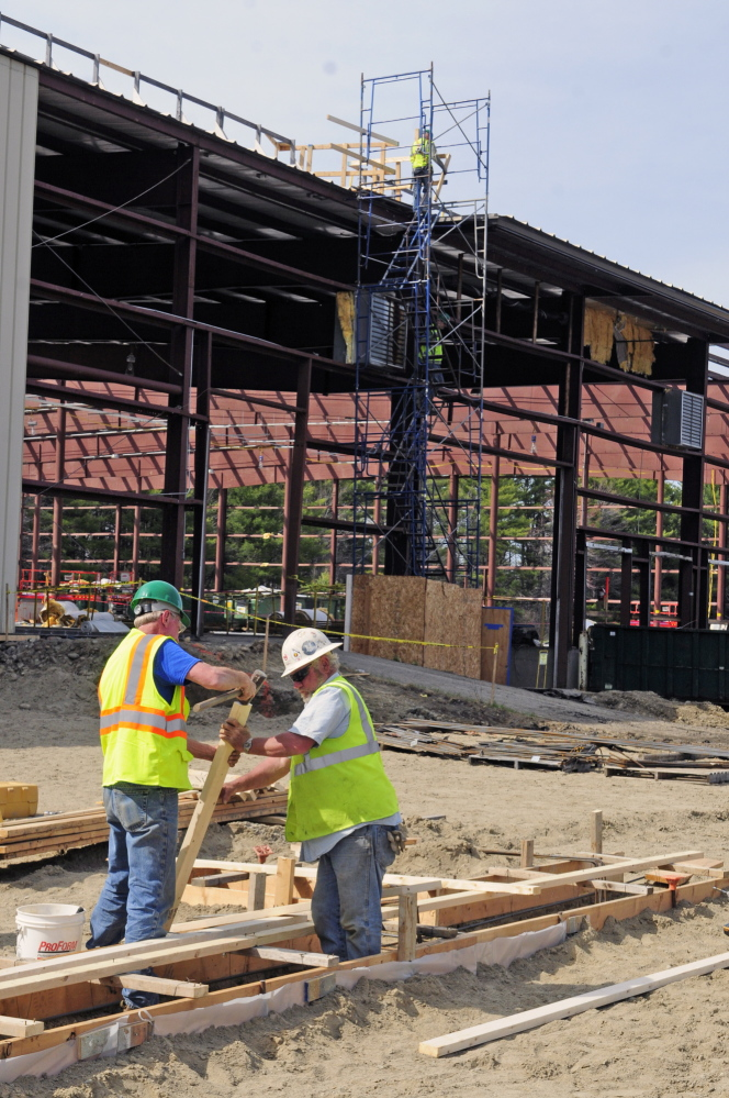 TRANSPORTATION MOVE: The state's future fleet maintenance site at 66 Industrial Drive, where workers in the foreground are building forms for an addition where trucks can be painted and workers in the background on scaffolding remove the roof from the former warehouse on the site.