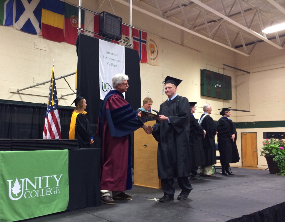 Unity College graduate Jacob A. Brodie '14, walks across the stage after receiving his diploma from President Stephen Mulkey at Saturday's commecement on May 10, 2014. Staff photo by Rachel Ohm.