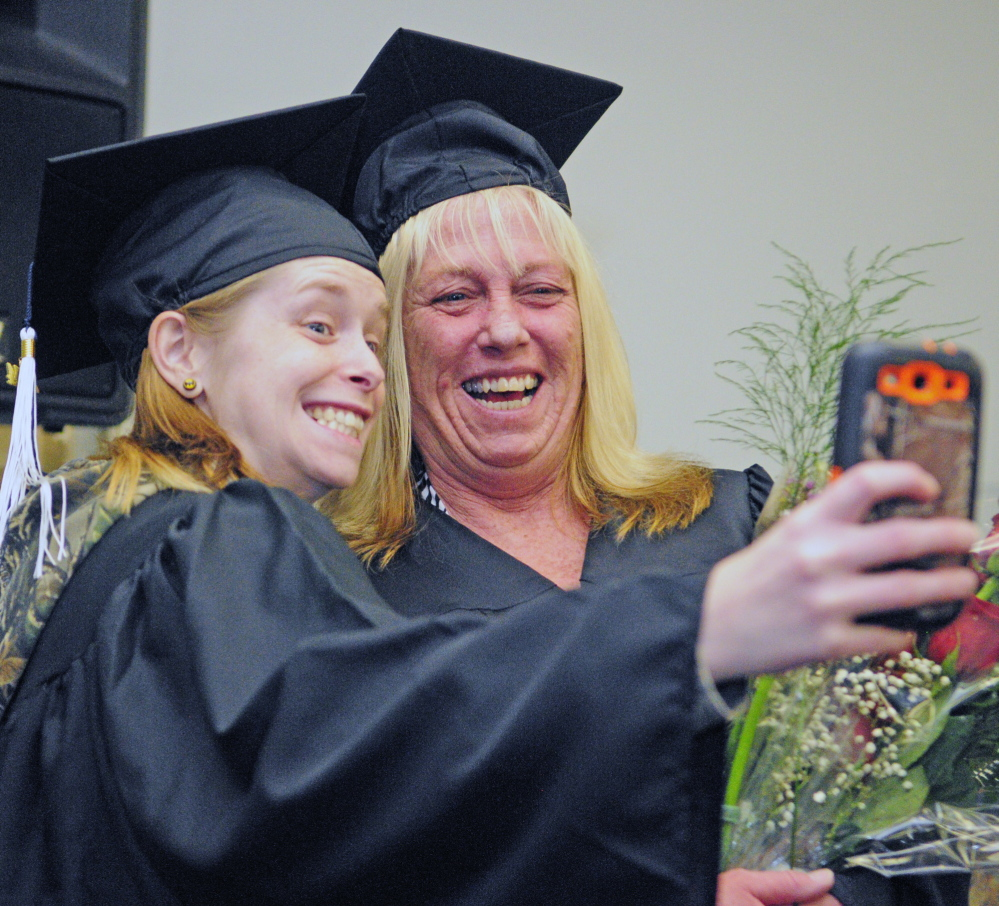"Staff photo by Joe Phelan RELATIVELY HAPPY: Nicole ""Sis"" Trask, left, of Hallowell takes a picture with her mother, Kathy Trask, before they walked in the University of Maine at Augusta graduation ceremony."