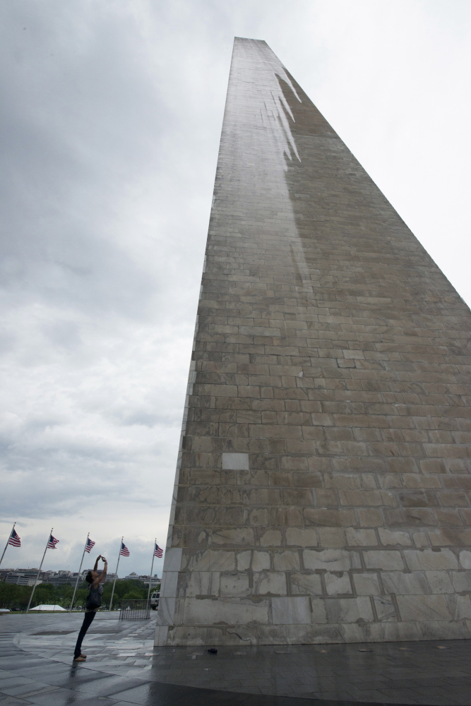 In this Saturday, May 10, 2014 photo, a journalist photographs the Washington Monument during a press preview prior to the re-opening of the monument, in Washington.