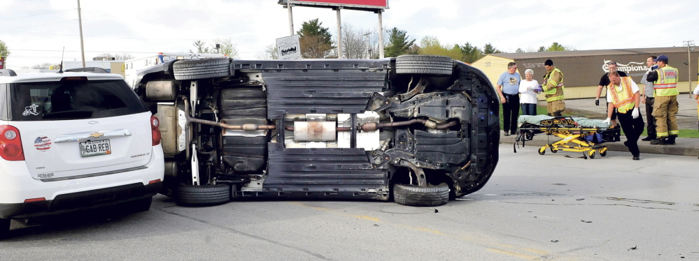 HARD COLLISION: A Suzuki car lies on its side following an accident on Main Street in Waterville early Sunday, May 11, 2014, while a person involved in the accident is treated to the right.