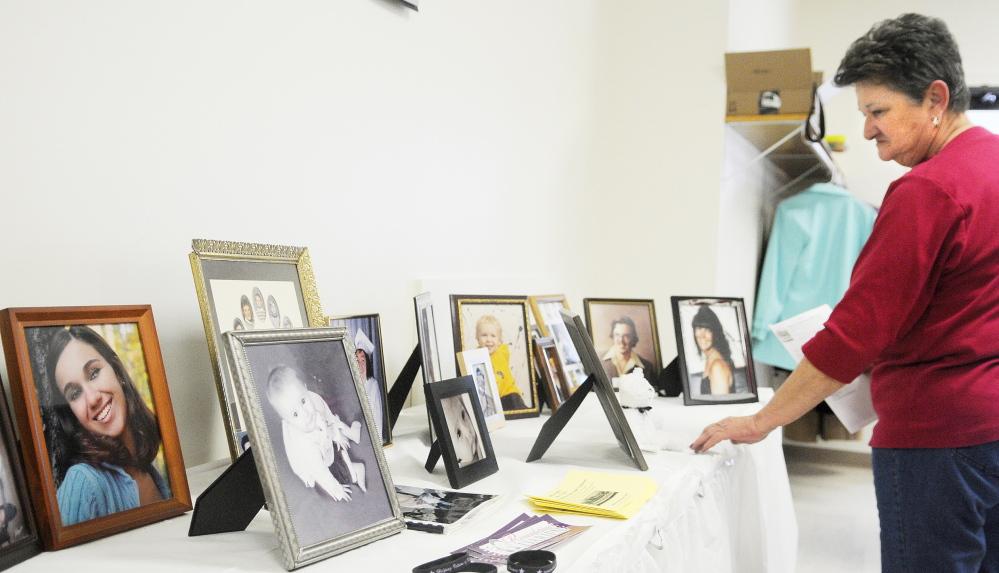 Remembering: Mary Wakefield examines photos of homicide victims in April during the annual luncheon of the Maine chapter of Parents of Murdered Children in Augusta. The group is holding a benefit supper on Saturday to raise money for a memorial.