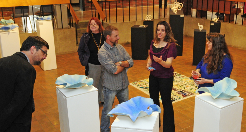 Porcelain: Adriana Love, second from right, talks about her blue porcelain pieces with visitors at the opening for the Senior Art Show on Saturday May 10, 2014 in the Danforth Gallery at the University of Maine at Augusta.