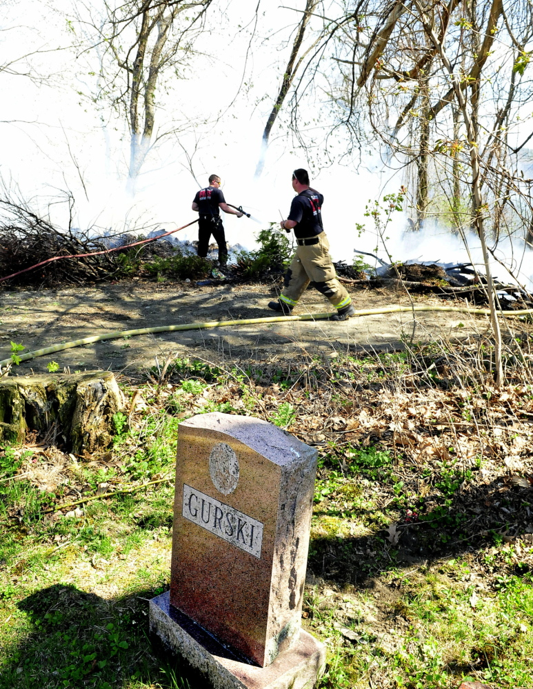 GRAVE CONDITION: Waterville firefighters battle a wind-swept fire in brush and the woods near grave sites that started at the rear of Pine Grove Cemetery on Monday.