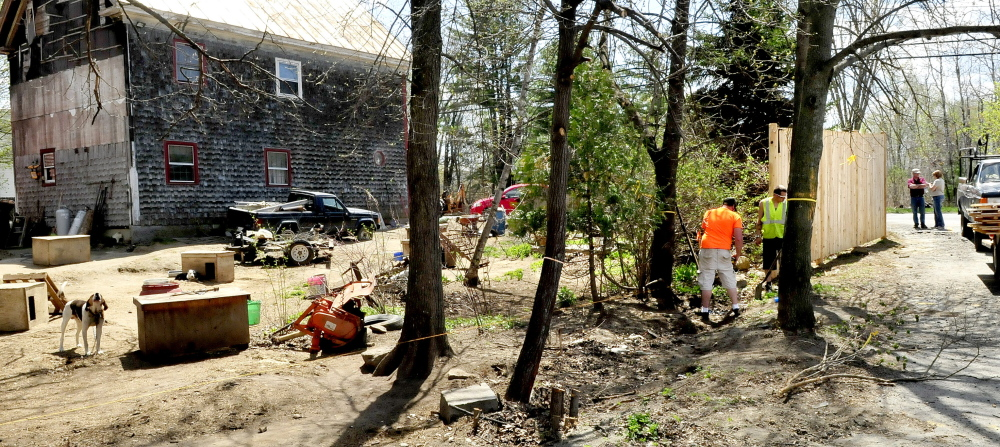 GOING UP: Paul Brann and Vinny Varanelli of Pine Tree Fence erect portions of stockade fence between the New Balance factory parking lot and abutting neighbors John and Lisa Ames and their dozens of hunting dogs in Norridgewock. Company facility managers Lewis Devoe and Angie Arbour observe the work in background.