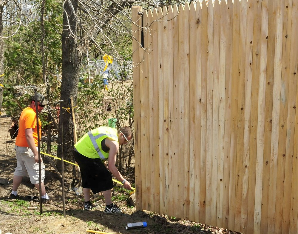 GOOD NEIGHBORS: Paul Brann, left, and Vinny Varanelli of Pine Tree Fence erect stockade fence between the New Balance factory parking lot in Norridgewock and abutting neighbors John and Lisa Ames on Monday.
