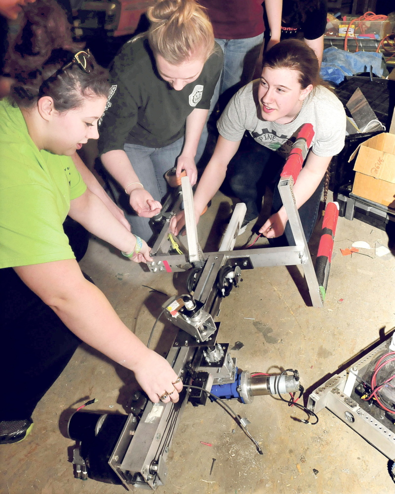 BRIGHT FUTURES: Messalonskee High School Robotics team members make repairs to the claw of the team's robot, which competed in the national championship in St. Louis. From left are Sydney O'Neal, Dakota Condon and Gretchen Rice.