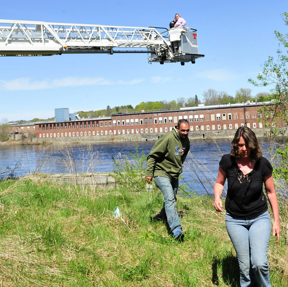 REUNITED: Joe Bradley and Darlene Champagne move as Waterville firefighter Mark Hamilton brings Mary Temple back to the ground in a department ladder truck bucket Tuesday after rescuing her from a granite abutment beside the Kennebec River at Head of Falls in Waterville. Temple said she feared climbing down the steep structure.