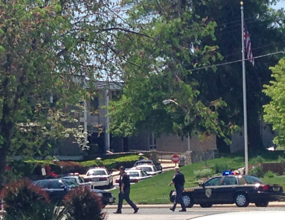 Police officers walk near WMAR-TV on Tuesday in Towson Md. Baltimore County police say a vehicle rammed a television station. A hole the size of several garage doors could be seen in the front of the building Tuesday afternoon.