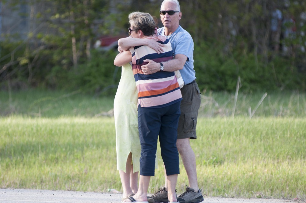 Neighborhood residents embrace after a police officer was fatally wounded at a home in Brentwood, N.H., on Monday.