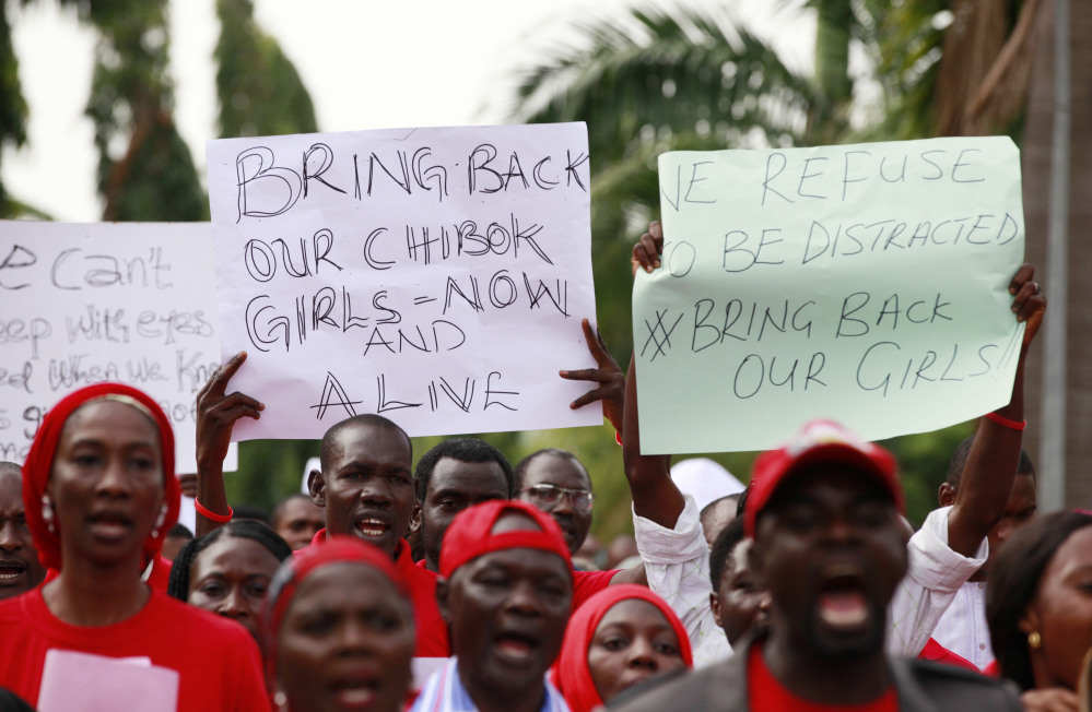 "People attend a demonstration calling on the government to rescue the kidnapped schoolgirls of the Chibok secondary school, in Abuja, Nigeria, Tuesday, May 13, 2014. A Nigerian government official said ""all options are open"" in efforts to rescue almost 300 abducted schoolgirls from their captors as US reconnaissance aircraft started flying over this West African country in a search effort. Boko Haram, the militant group that kidnapped the girls last month from a school in Borno state, had released a video yesterday purporting to show some of the girls. A civic leader said representatives of the missing girls' families were set to view the video as a group later today to see if some of the girls can be identified. (AP Photo / Sunday Alamba)"