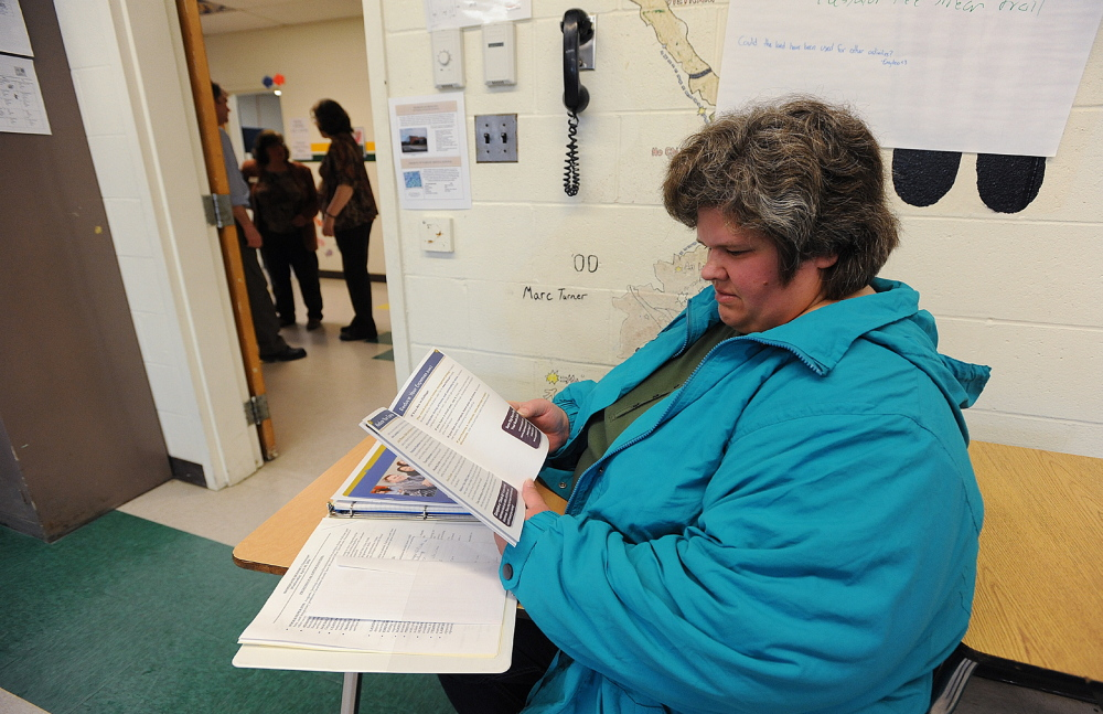 FACING UNEMPLOYMENT: United Technologies employee Darlene Chamberlain of Pittsfield reads a booklet on how to take steps to financial sucess while waiting with other job seekers at a career workshop during a job fair in Pittsfield on Wednesday. Chamberlain will lose her job when UTC closes.