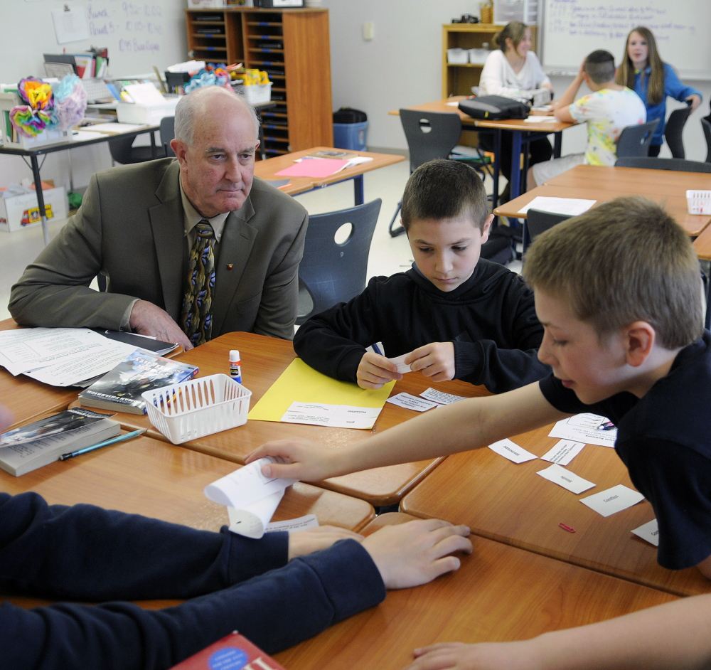 MAKING THE GRADE: Education Commissioner Jim Rier observes Cony Junior High students Wednesday as they work on a language arts problem at the Augusta school.