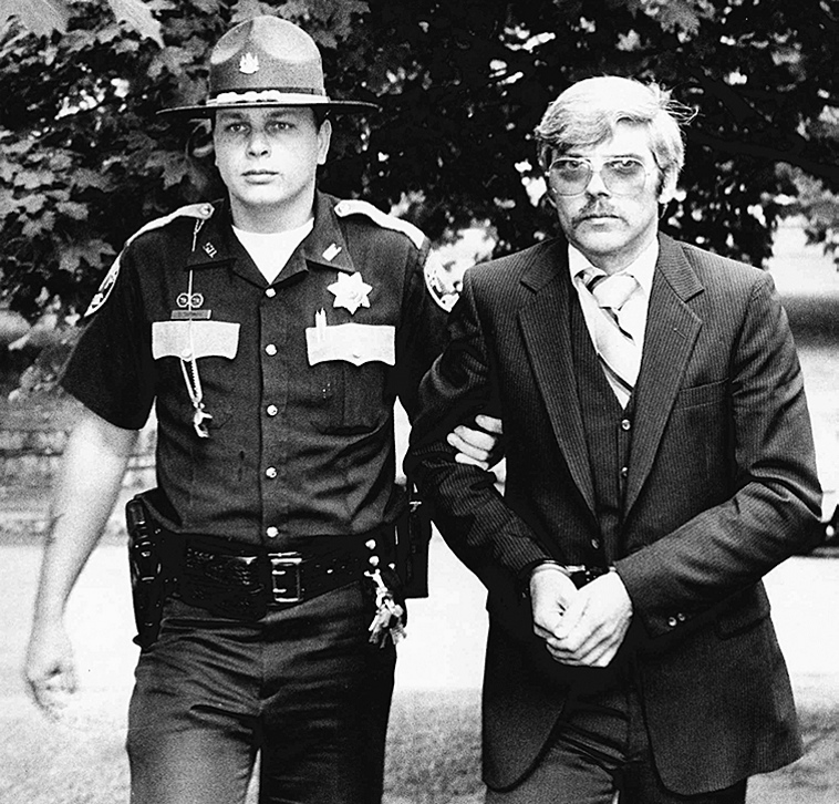 Caught: Michael Boucher, right, is escorted by Kennebec County Sheriff's Deputy Eric Testerman in this July 9, 1991, file photo.