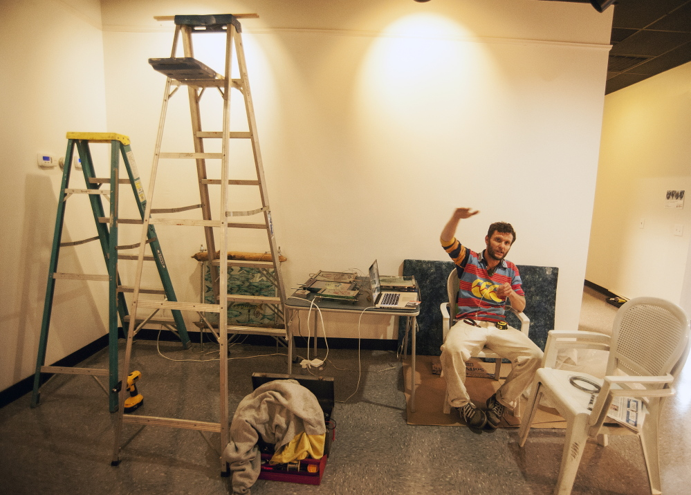 NEW LOBBY: Local artist Thom Klepach prepares a work of art to be hung on the new walls of the lobby at Railroad Square Cinemas in Waterville on Thursday.