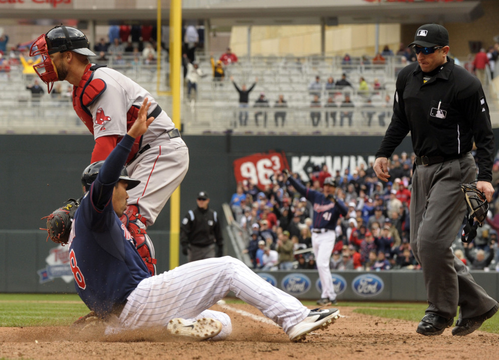 Twins catcher Kurt Suzuk slides past Red Sox catcher David Ross with the winning run in the 10th inning Thursday. Home plate umpire Chris Guccione, right, looks in to make the call. Minnesota won 4-3.